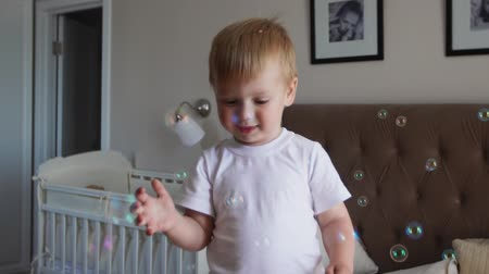 saltando : A boy in a white T-shirt and blue jeans catches soap bubbles standing on the bed in the parent bedroom Stock Footage