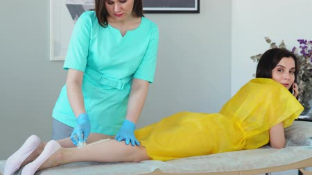woman waxing : The girl talks on the phone and smiles during hair removal on her legs. Shugaring master removes hair from legs