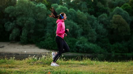 спортивная одежда : A morning jog in the Park near the pond in the Sunny rays of dawn, the girl is preparing to Mariano and lead a healthy lifestyle Стоковые видеозаписи