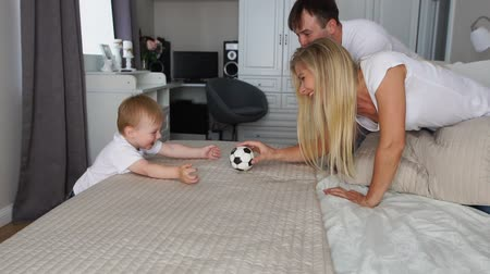 łaskotki : Dad and mom play with the boy on the bed with the ball