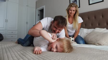 łaskotki : Mom and father tickling her child. people, family, fun and morning concept - happy child with parents tickling in bed at home. Happy family spending time together in bedtime playing and hugging Wideo