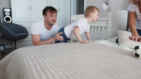 сестры : Family spending free time at home. Cheerful family having fun with their daughters on the bed