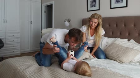 pluma : Mom and father tickling her child. people, family, fun and morning concept - happy child with parents tickling in bed at home. Happy family spending time together in bedtime playing and hugging Stock Footage