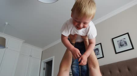 acrobats : Dad keeps a dignity above himself lying on the bed. A boy in a white T-shirt laughs and smiles from playing with his father
