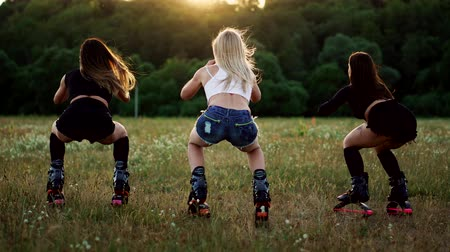 amincissant : Group training kangoo. Three girls at sunset perform dynamic squats aimed at slimming and strengthening the muscles of the thighs