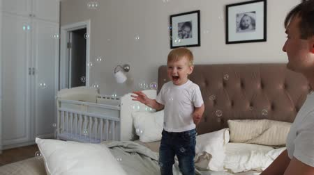 acrobats : Caring father plays son looking at soap bubbles, the boy is happy jumping on the bed