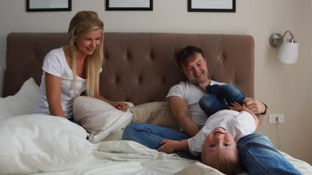 minder : Happy family playing to pillows fight on bed at home
