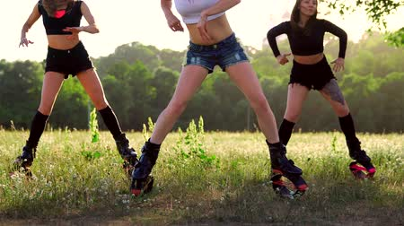 buty sportowe : Group training kangoo. Three girls at sunset in the Park doing fitness