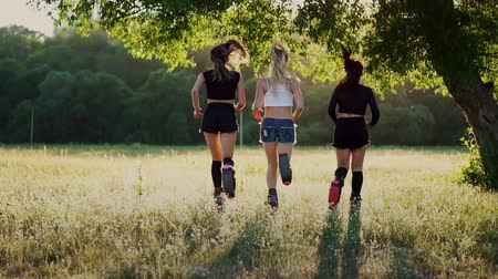 molas : Three girls in boots with springs running through the summer Park at sunset doing sports