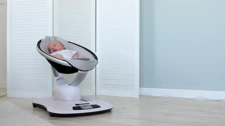comfortable seat : Sweet newborn baby girl sleeping in a bouncer chair in a white room Stock Footage
