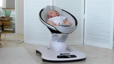 нежный : Modern high-tech rocking chair helps parents put the child to bed. White interior of childrens room Стоковые видеозаписи