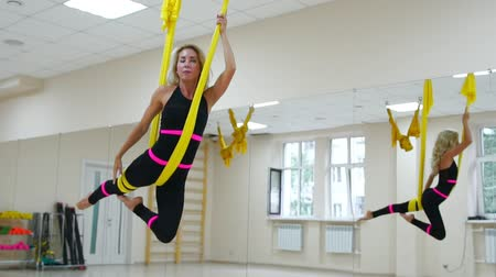 süspansiyon : Young beautiful woman doing aerial yoga practice in purple hammock in fitness club.
