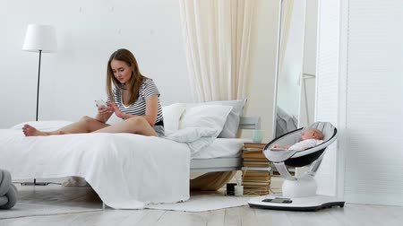 sörf : In the white bedroom is engaged in online shopping while on maternity leave, chooses a dress through the phone, next to a sleeping baby in a chair Stok Video