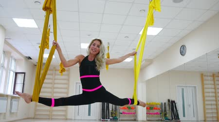 pozíció : Young beautiful yogi woman doing aerial yoga practice in purple hammock in fitness club