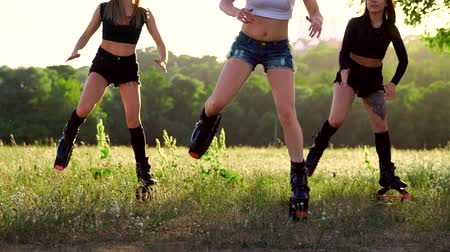 ação : Group training kangoo. Three girls at sunset in the Park doing fitness