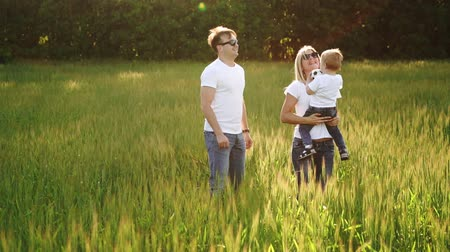 три человека : Family Walking In Field Carrying Young Baby Son