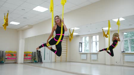 hamak : Young beautiful woman doing aerial yoga practice in purple hammock in fitness club.