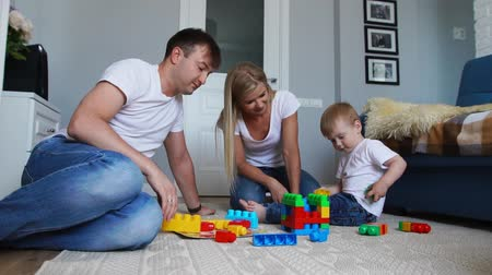 menino : Happy family dad mom and baby 2 years playing building blocks in their bright living room. Slow-motion shooting happy family