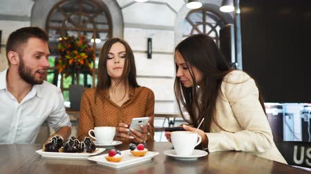 socialising : A group of men and women in office clothes sitting in a cafe at a large table and show each other in mobile phones funny pictures Stock Footage