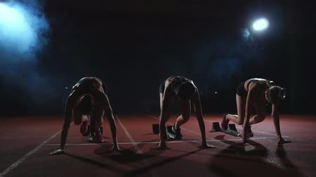 athletes foot : Female runners at athletics track crouching at the starting blocks before a race. In slow motion.