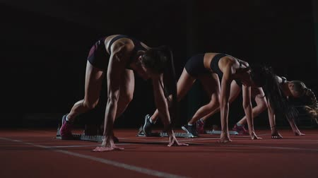 começando : Female runners at athletics track crouching at the starting blocks before a race. In slow motion.