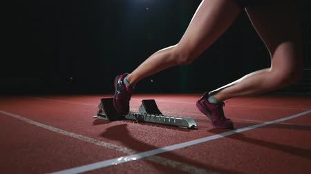 começando : Female hispanic athlete training at running track in the dark. Slow motion