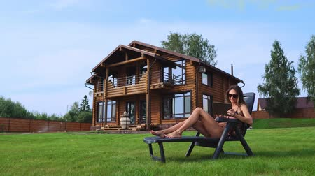 seçkinler : A beautiful slender woman lies on a sun lounger in a swimsuit with a tablet on the background of a large country house in sunglasses and works remotely on vacation Stok Video