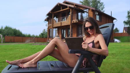 элита : A beautiful slender woman lies on a chaise longue in a swimsuit with a tablet on the background of a large country house in sunglasses and sunbathes in the sun viewing photos on social networks Стоковые видеозаписи