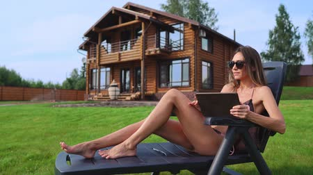 seçkinler : A beautiful brunette in a swimsuit lying on a sun lounger near her chic mansion with large Windows smiles while working at home remotely via the Internet in the business sphere. The concept of country life Stok Video