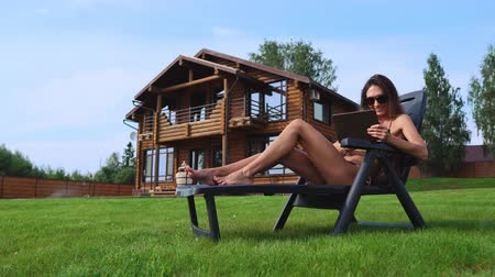 seçkinler : A beautiful brunette in a swimsuit lying on a sun lounger near her chic mansion with large Windows smiles and waves her hand to friends and works remotely on a tablet computer Stok Video