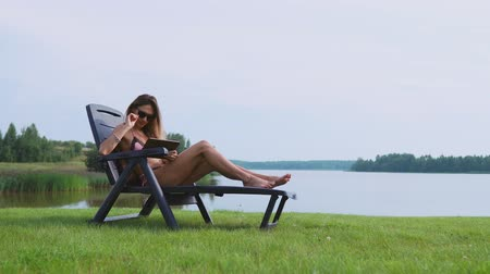 elite : Woman working on a tablet computer traveling the world on vacation, sunbathing on the beach near the lake