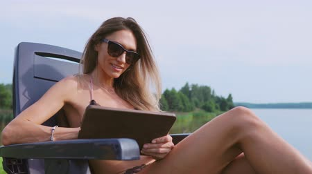 elite : Sexy girl blogger in a swimsuit writes messages through the tablet computer about the chic country life in social networks. Shares his impressions of the rest