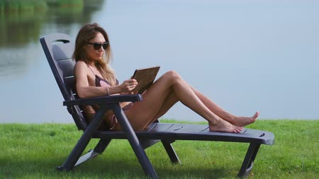 エリート : Woman lying on a sun lounger in a swimsuit with a tablet computer finger touches the screen of the tablet and smiles lying on the lake