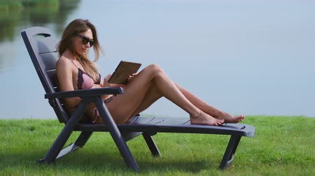 элита : Slim woman lying in sunglasses on a sun lounger in a swimsuit with a tablet computer finger touches the screen of the tablet and smiles lying on the lake
