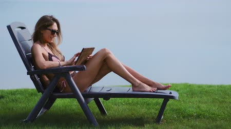 elite : Beautiful brunette in a swimsuit lying on a sun lounger on the lake smiling working remotely via the Internet in the business sphere. The concept of country life