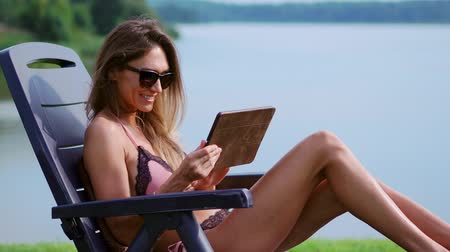 escrever : Beautiful brunette in a swimsuit lying on a sun lounger on the lake smiling working remotely via the Internet in the business sphere. The concept of country life