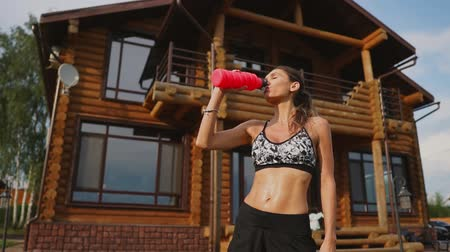 sports nutrition : Curve brunette with inflated abdominal muscles drinking protein after a workout against the backdrop of huge houses with big Windows Stock Footage