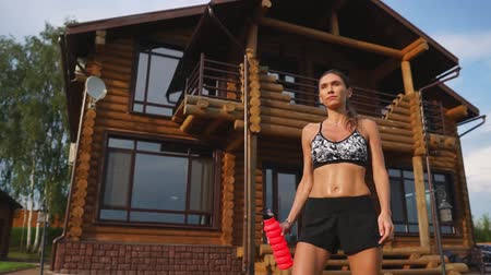 sports nutrition : Sexy brunette in a black top and shorts after a workout goes wet near her huge mansion and drinks water from the bottle
