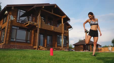 cardio workout : A slim and beautiful woman in sportswear with an open press is preparing to start training on the lawn near her home flexing her legs, knees, shins and thighs with warming up exercises Stock Footage