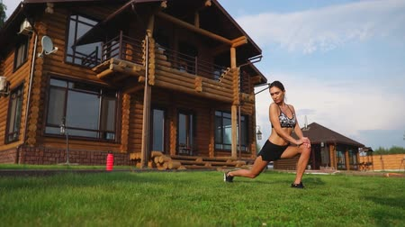 heart rate : A slim and beautiful woman in sportswear with an open press is preparing to start training on the lawn near her home flexing her legs, knees, shins and thighs with warming up exercises Stock Footage