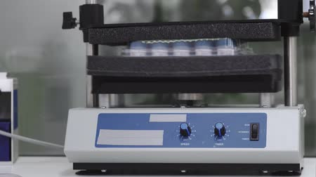health test : Machine for shaking test tubes by vibration to separate the cells and to continue studies Stock Footage