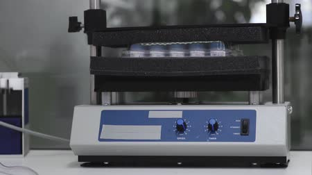 produtos químicos : Machine for shaking test tubes by vibration to separate the cells and to continue studies Stock Footage