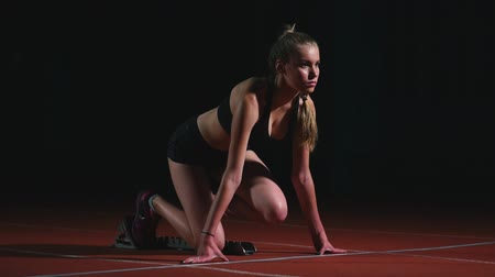 pista de corridas : Female athlete on a dark background to run the sprint of the cross country pad on the treadmill on a dark background Stock Footage