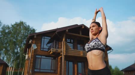pozíció : Woman on the grass doing yoga on the background of a beautiful house. The concept of a healthy lifestyle Stock mozgókép