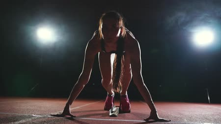 pista de corridas : Professional woman athlete on a dark background to run the sprint of Jogging shoes in sneakers on the track of the stadium on a dark background Stock Footage