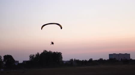 скольжение : The pilot on a paraglider flies in the sky over sunset and night landscape. background Стоковые видеозаписи