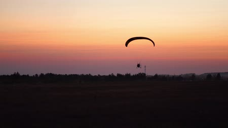 padák : The pilot on a paraglider flies in the sky after sunset with orange . background