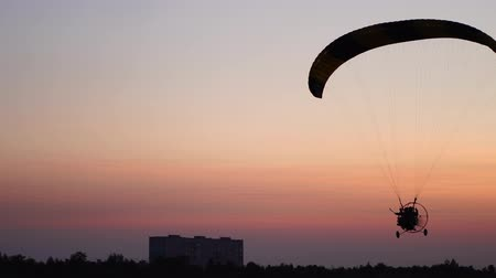 рекреационных преследования : The pilot on a paraglider flies from the camera gradually moving away into the distance against the sunset beautiful sky.