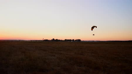 hang gliding : Pilot flying a paraglider with a motor at sunset, the camera on the suspension moves along the field