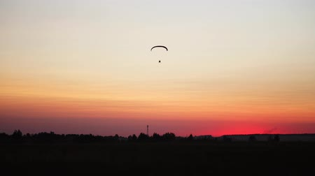 hang gliding : The pilot on a paraglider flies from the camera gradually moving away into the distance against the sunset beautiful sky. Beautiful background background picture. concept of freedom Stock Footage